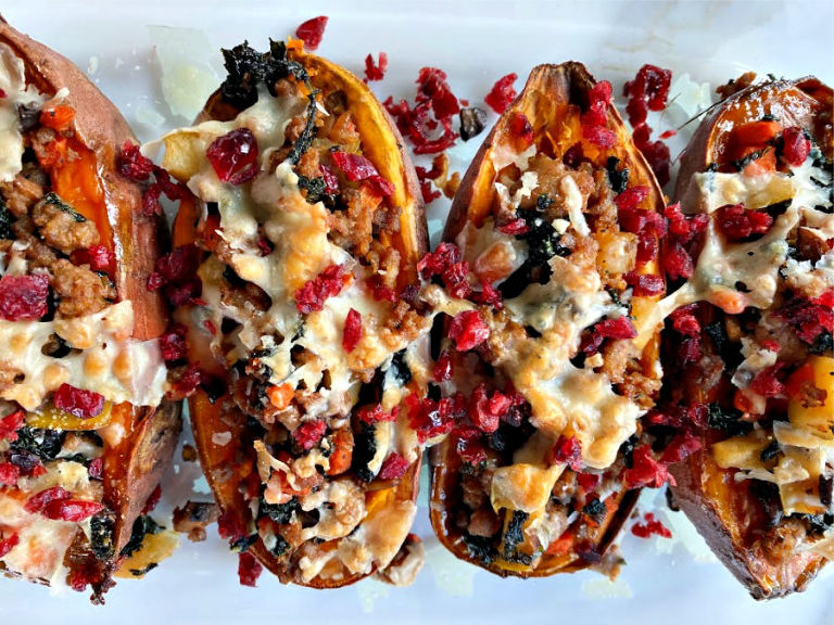 Simple, mouthwatering stuffed sweet potatoes! Savory sausage, kale, garlic and the bright pop of dried cranberries makes this a flavor packed weeknight meal! Paleo optional and gluten free!